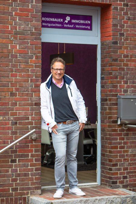 Immobilienmakler Michael Rosenbauer steht im Eingang seiner Immobilienfiliale
